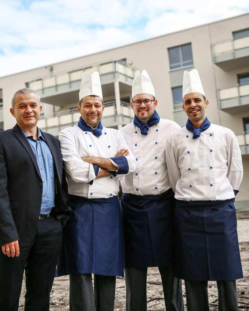 Christian Ewalt, ein Mann in Anzug, steht neben drei Köchen in weißen Kitteln.
