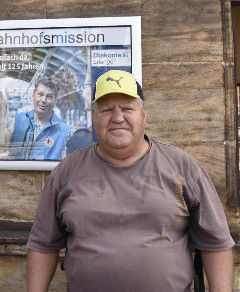 Ein Mann mit Käppie und T-Shirt steht vor dem Eingang der Bahnhofsmission.