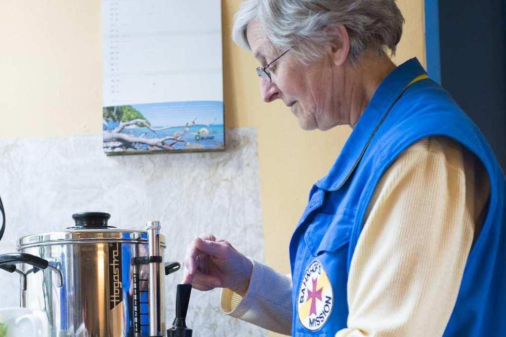Eine ältere Mitarbeiterin der Bahnhofsmission mit Brille schenkt Kaffee aus.