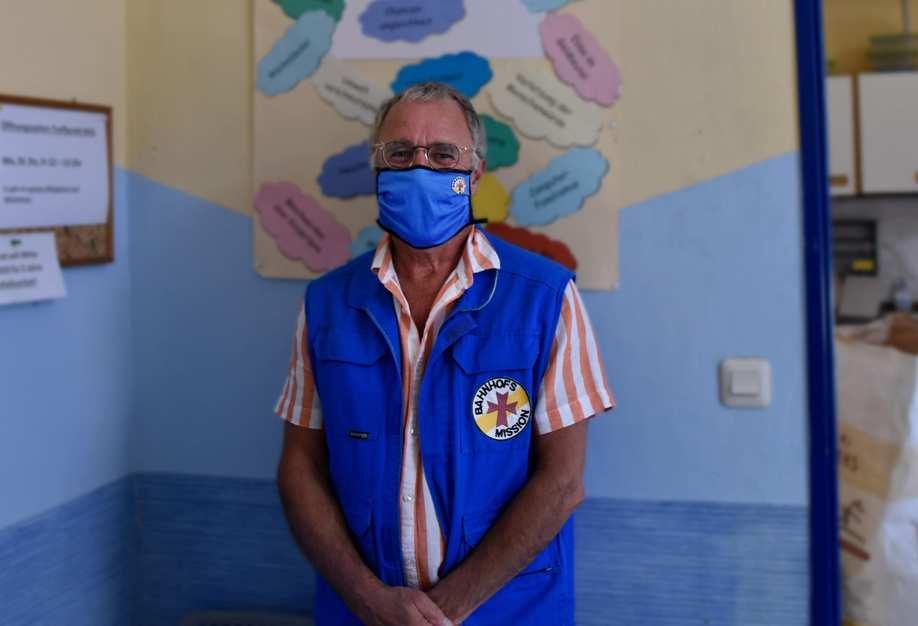 Ein Mitarbeitender mit Weste und Mundschutz der Bahnhofsmission in den Räumen der Organisation.