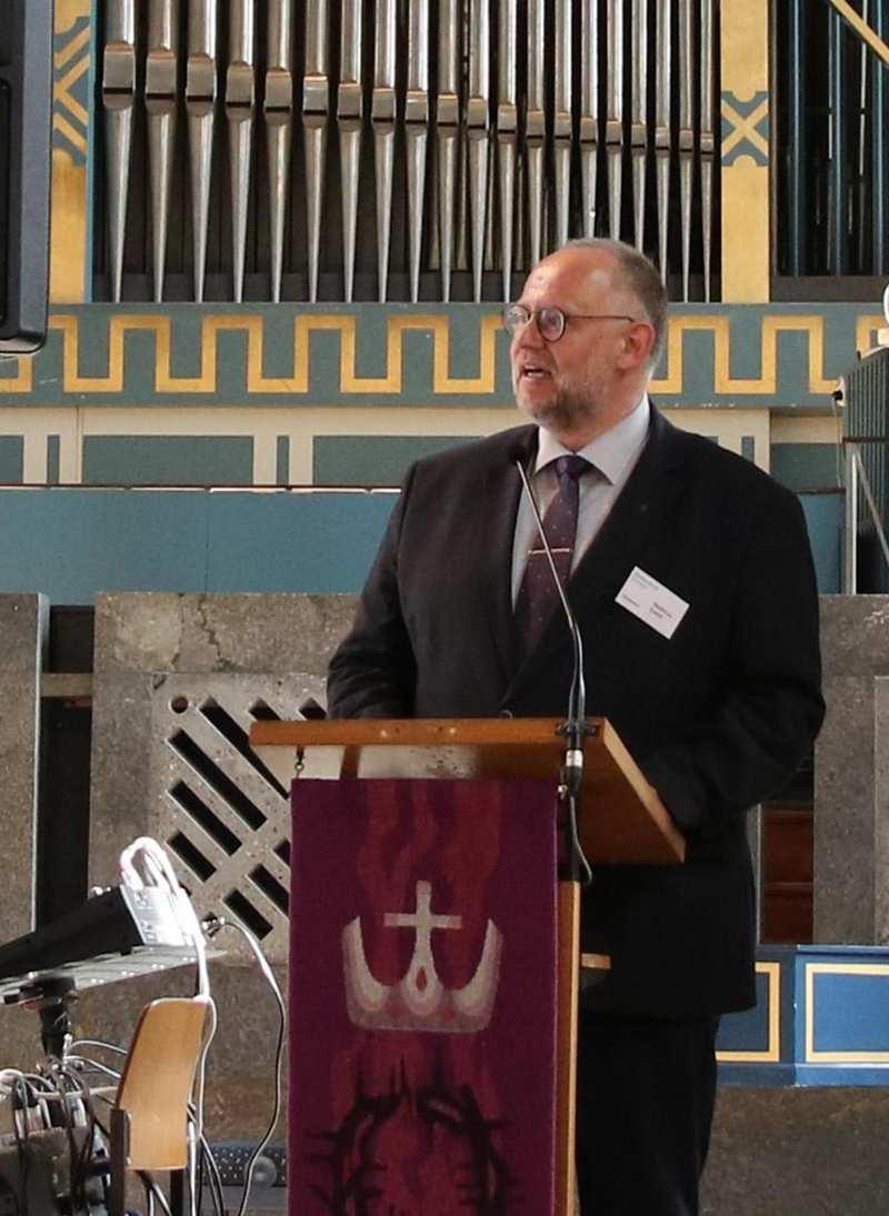 Ein Mann steht im Altarraum einer KIrche an einem Pult. Im Hintergrund ist eine Orgel.