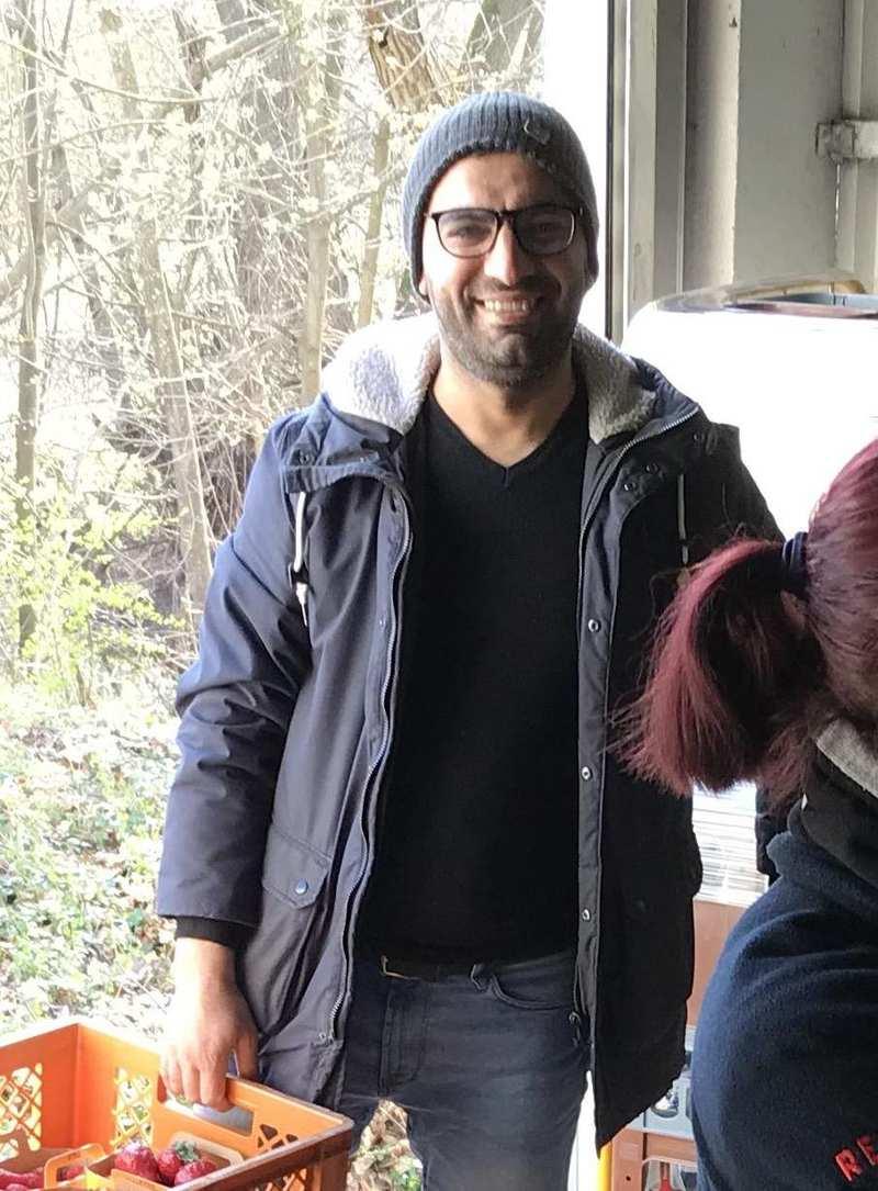 Ein Mann mit Brille und Wollmütze trägt eine Kiste mit Lebensmittel.