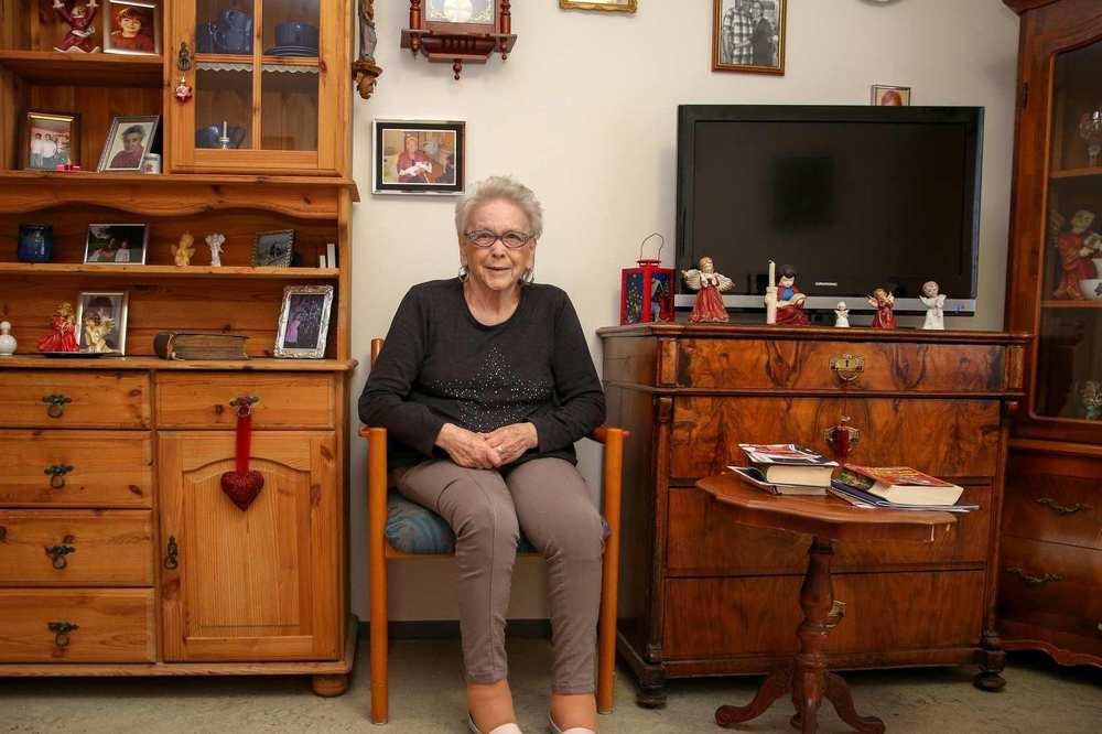 Eine ältere Frau sitzt in ihrem Zimmer. An der Wand hängen verschiedene Bilder, die Inneneinrichtung ist holzvertäfelt.