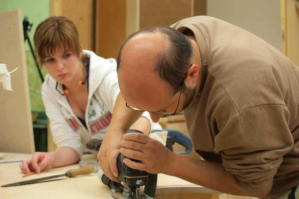 Ein Mann mit Brille arbeitet mit einer Stichsäge. Eine junge Frau sieht ihm dabei zu.