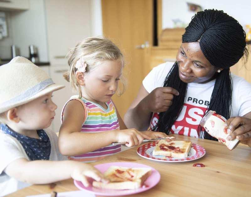 Eine Frau, ein kleiner Junge und ein Mädchen sitzen zusammen am Esstisch und lächeln sich an.