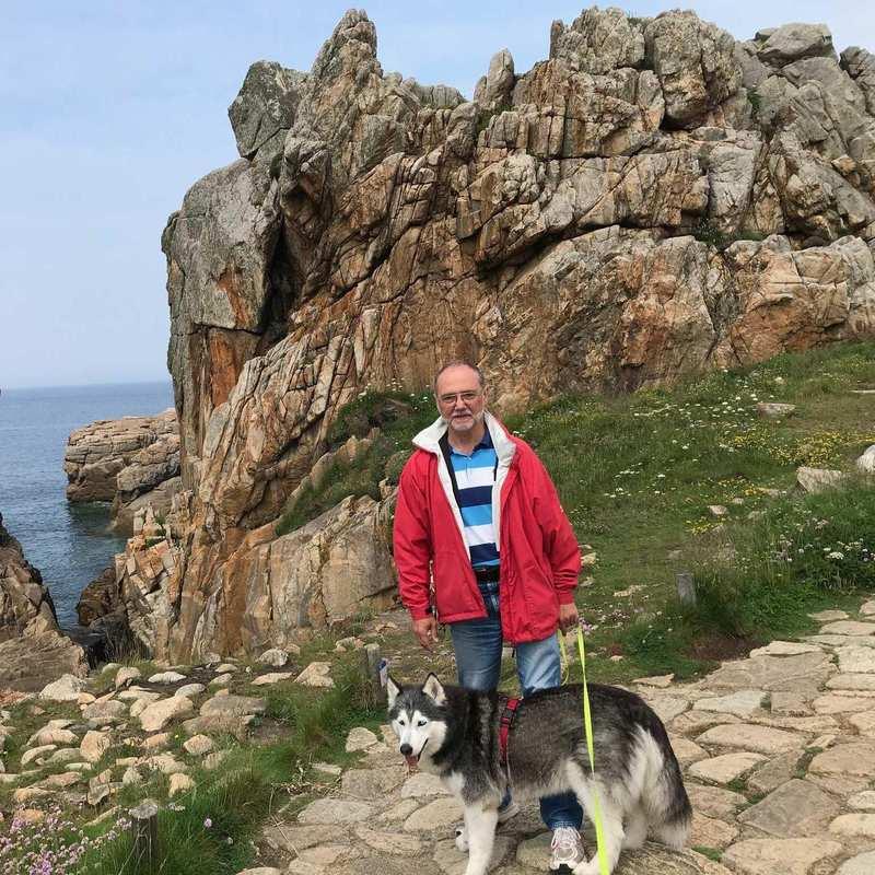 Ein Mann steht auf einem felsigen Wanderweg. Zwischen den Felsen schimmert das Meer. Vor ihm sitzt ein Husky.