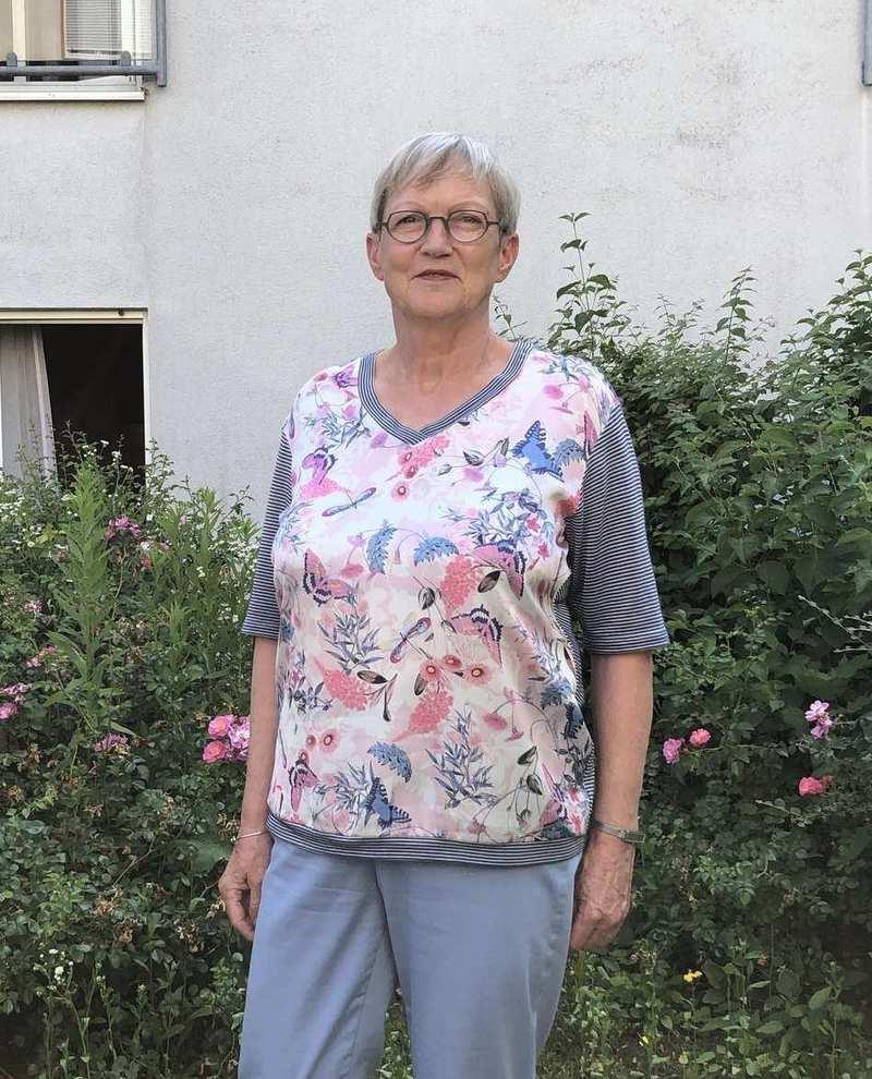 Ingrid Reise, eine ältere Frau mit kurzgeschnittenen grauen Haaren vor einem blühenden Strauch.