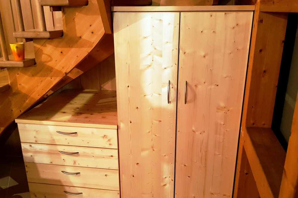 Ein doppeltüriger Schrank, daneben eine kleinere Ablage mit fünf Schubladen. Beide Möbelstücke stehen unter einer Holztreppe.