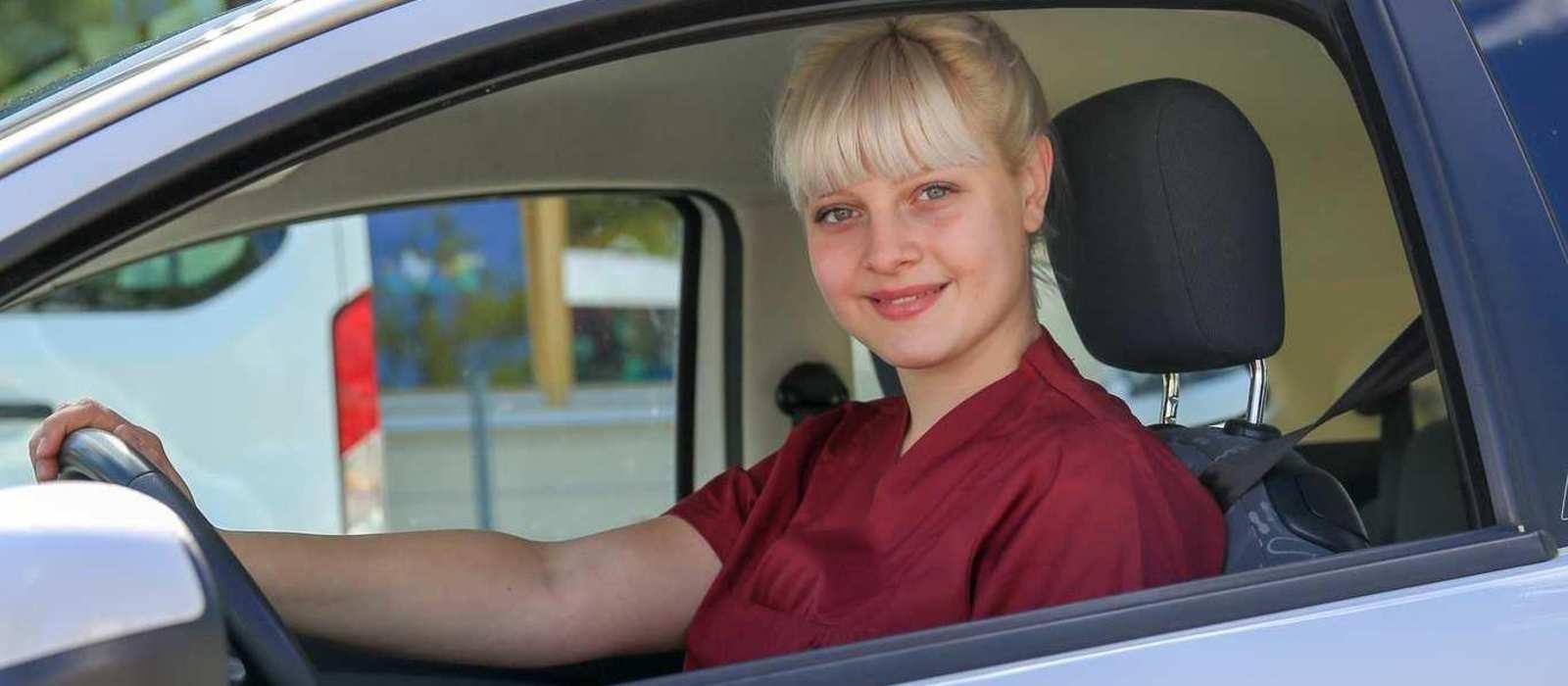 Eine Pflegekraft sitzt am Steuer eines Autos der Diakonie Erlangen.