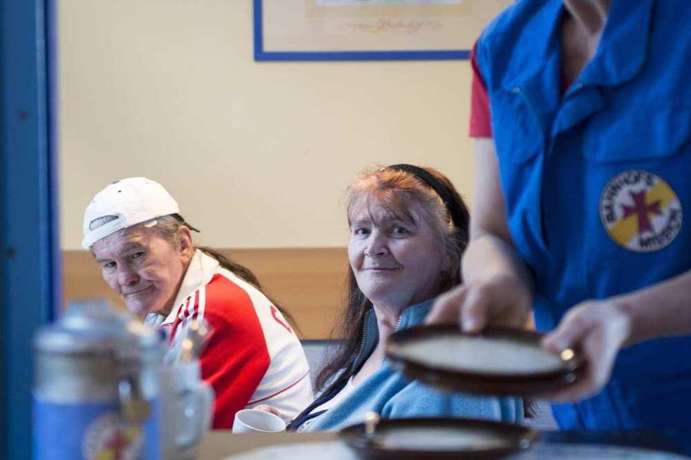 Eine Mitarbeiterin der Bahnhofsmission gibt Teller aus. Im Hintergrund sitzen zwei Gäste.