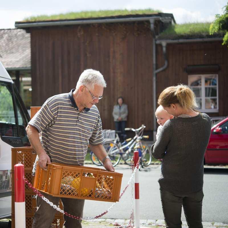 Ein Fahrer der Erlanger Tafel lädt Lebensmittel aus seinem Lieferwagen aus. Eine Frau mit Kleinkind steht daneben.