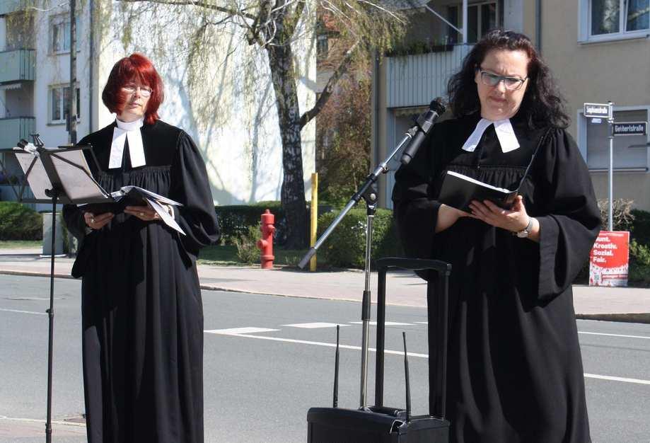 Zwei Pfarrerinnen im Talar stehen auf einem Gehsteig. Vor ihnen steht ein mobiler Lautsprecher.