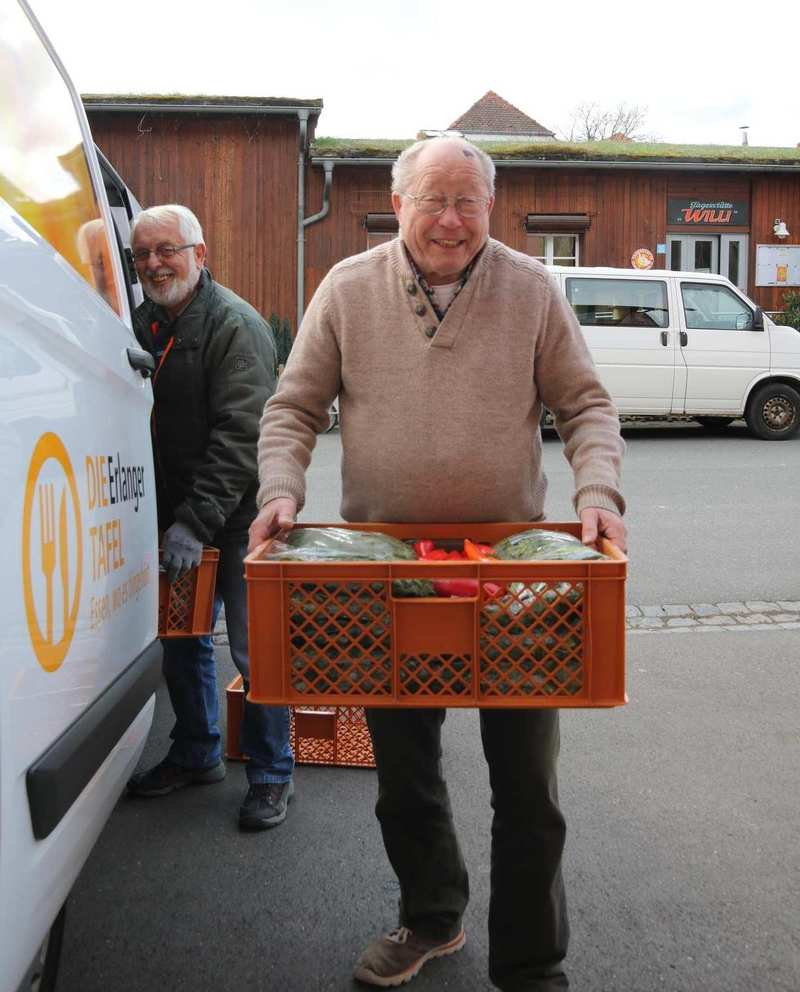 Ein älterer Mann lädt eine Kiste mit Lebensmittel aus dem Lieferwagen der Tafel Erlangen.