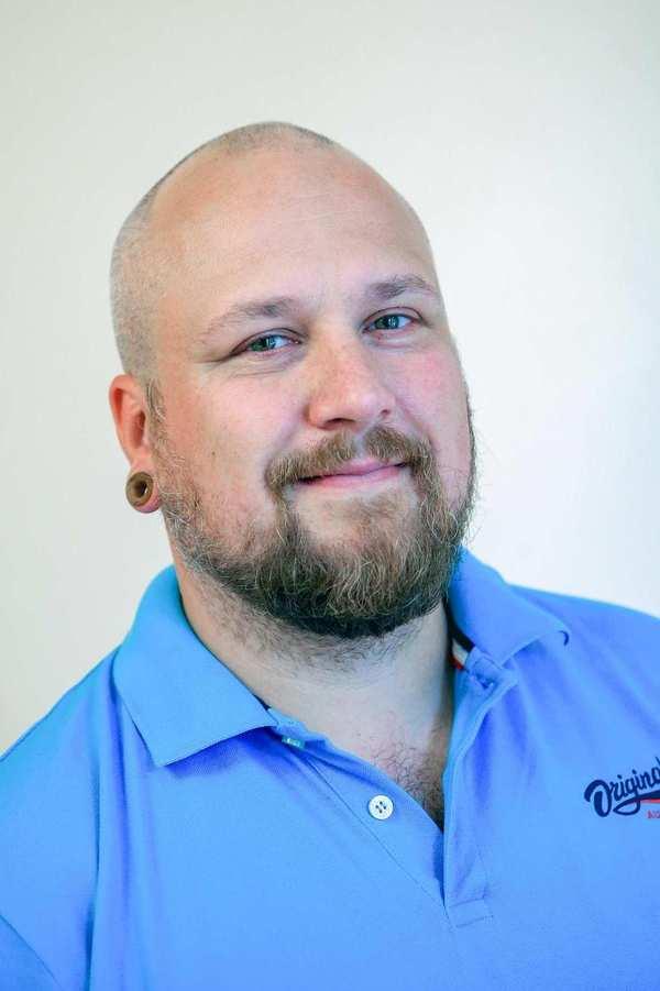 Alexander Kulla. Ein Mann mit Glatze und kurzgeschnittenem Bart.
