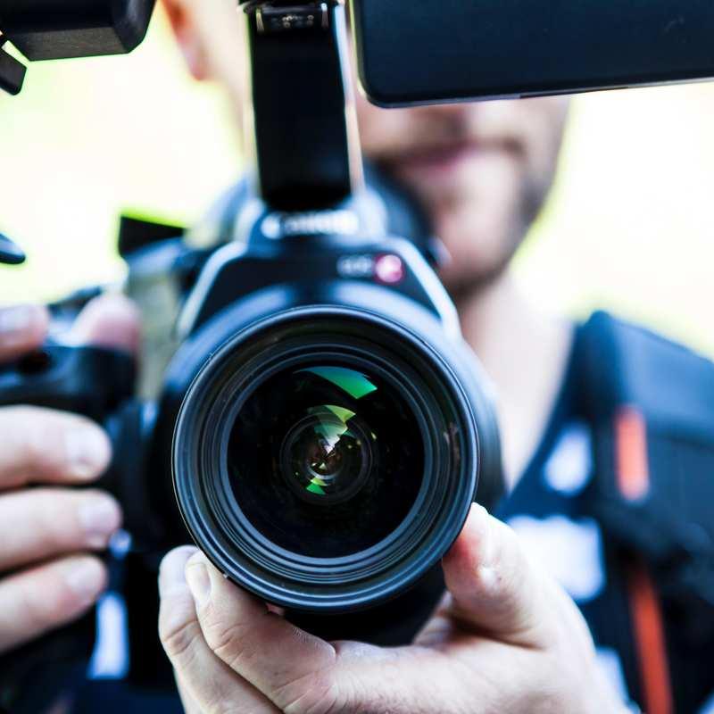 Das Objektiv einer Kamera. Im Hintergrund ist der Fotograf, der die Kamera in Händen hält, unscharf zu erkennen.
