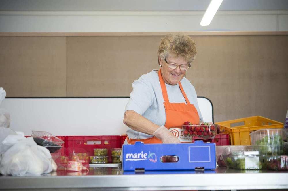 Eine Mitarbeiterin der Tafel hat ein Schälchen mit Erdbeeren in der Hand. Neben ihr liegen Weintrauben.