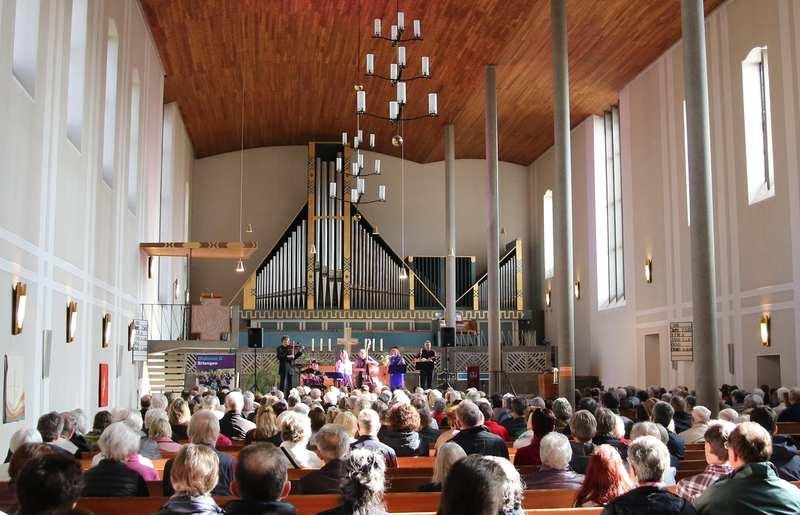 Das Langschiff einer Kirche. In der Bildmitte sitzen Besucherinnen in den Kirchenbänken. Im Hintergrund des Altarraums spielt eine Musikgruppe.