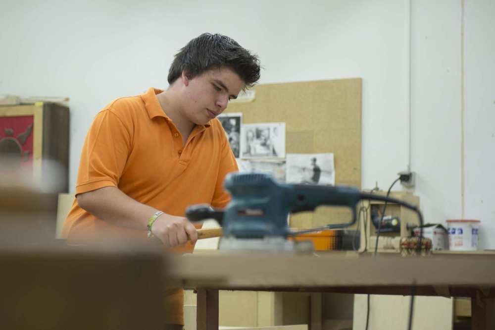 Ein Auszubildender steht mit einem Hammer an einer Werkbank. Im Vordergrund ist ein Schwingschleifer.