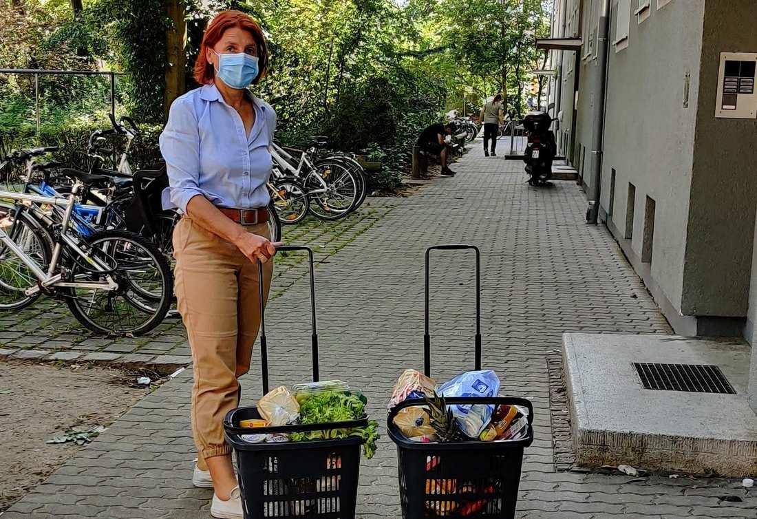 Eine Frau mit Mundschutz steht mit zwei Körben voller Lebensmittel vor einer Haustür.