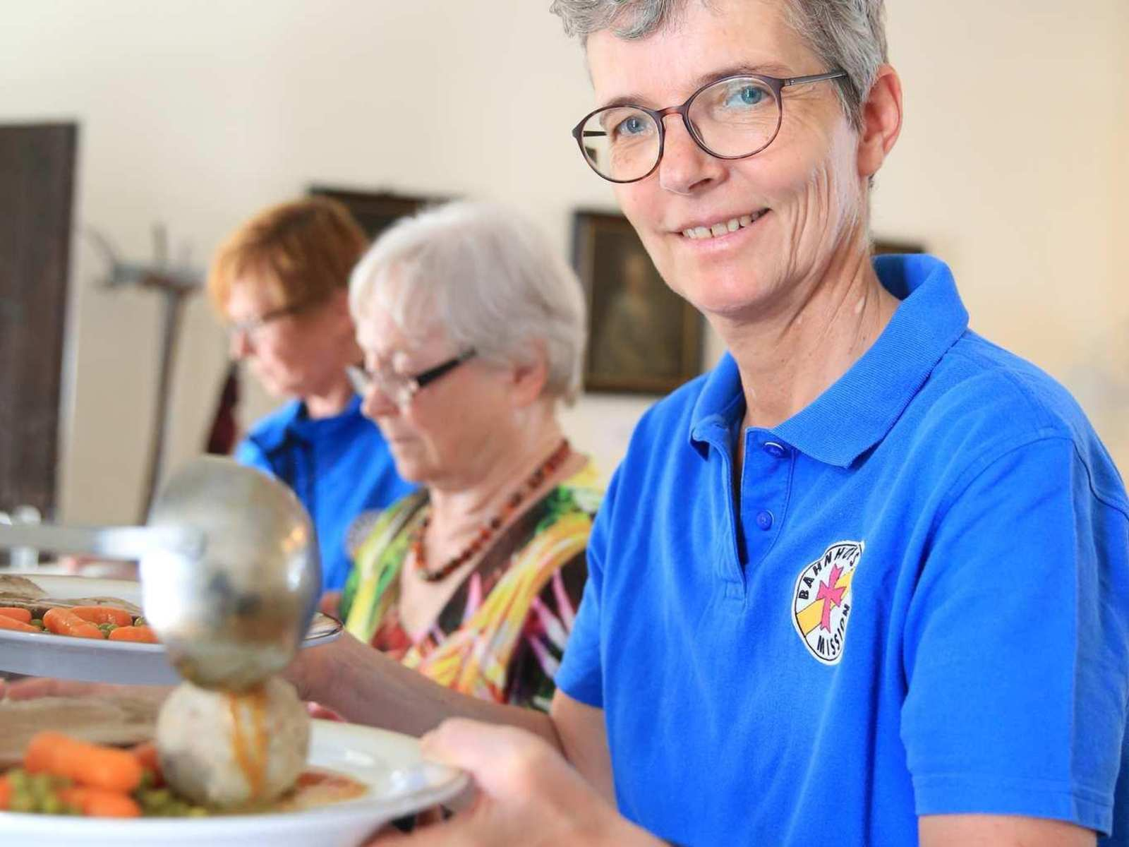 Eine Mitarbeitende der Bahnhofsmission richtet einen Teller mit Semmelknödel, Braten und Buttergemüse an.