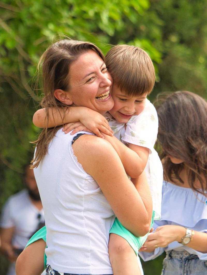 Eine glückliche Frau hat einen strahlenden Jungen auf dem Arm liebevoll umschlungen.