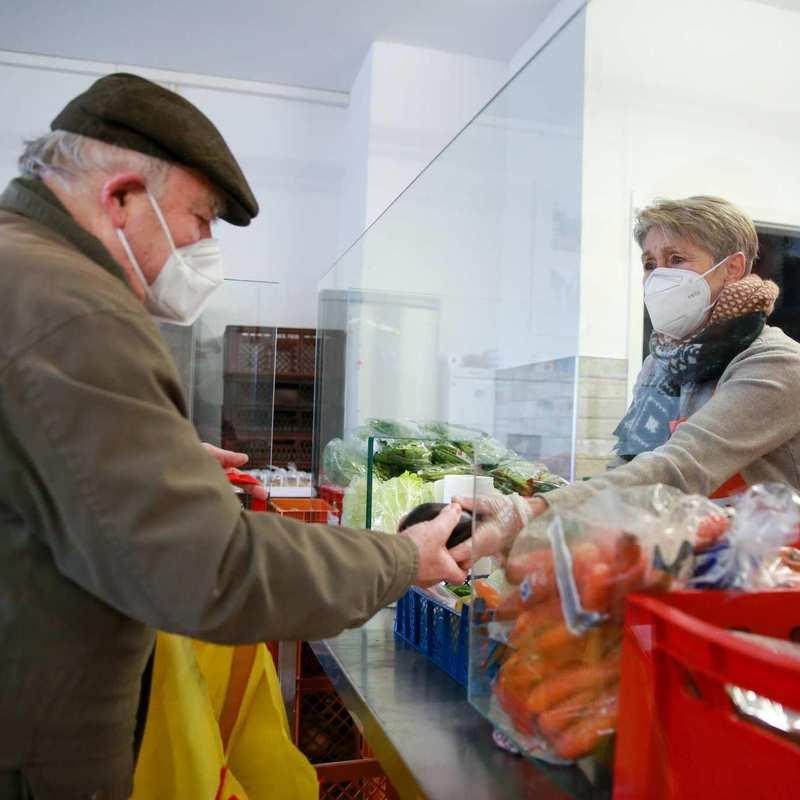 Eine Frau reicht einem alten Mann frische Lebensmittel durch eine Durchreiche.