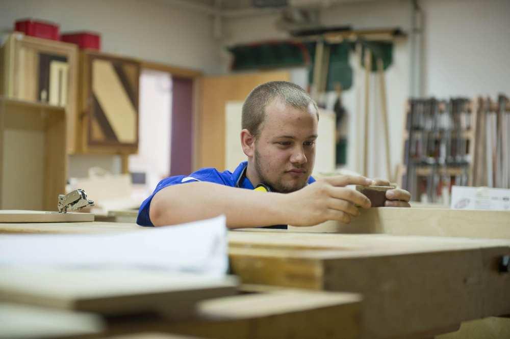 Ein junger Mann steht an einem Werkstück und passt ein Holzstück detailgenau an.
