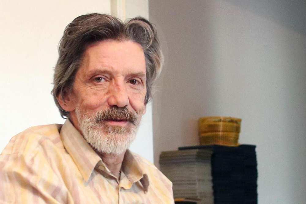 Ein älterer Mann mit Bart und längeren grauen Haaren sitzt in einem Sessel.